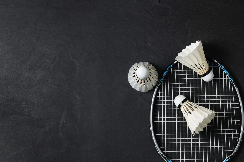Shuttlecocks and badminton racket on black background.Sport concept, Concept winner, Copy space image for your text