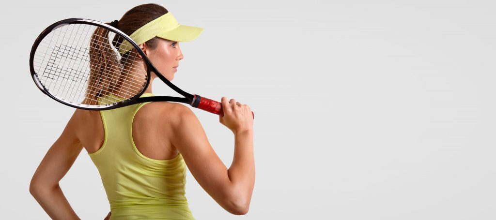 Back view of sporty female likes tennis, holds racquet, wears casual t shirt and cap, ready to play and compete, stands against white background with copy space for your advertisement or slogan