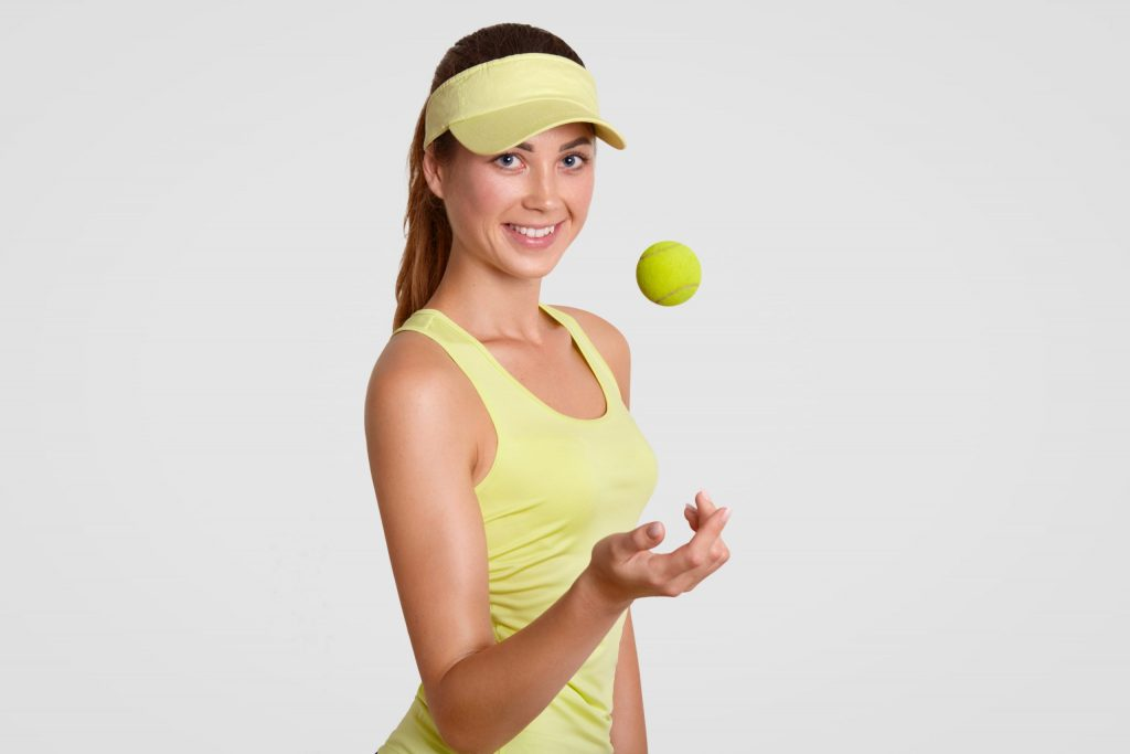 Horizontal shot of cheerful female tennis player with ball, dressed in casual sportswear, has slim healthy body, goes in for sport regularly, isolated over white background, prepares for tournament